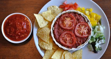 Tacopaj med veganska nachochips, tomatsås, paprika, tomat och sallad.